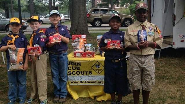 William Engbrecht, Joshua Ritter, Calvin Engbrecht, Chad Gibbs, and Cody Gibbs sell Boy Scout Popcorn at the Arlington Farmers Market on Wednesday to raise funds for outdoor activities for the pack.