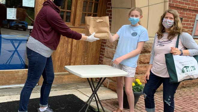 Substitute Librarian Aniela Anderson passes a bag of books and materials to Middleton residents Noelle Vanderwoude and her mom Jill at the Flint Library curbside pickup on June 11, 2020.
