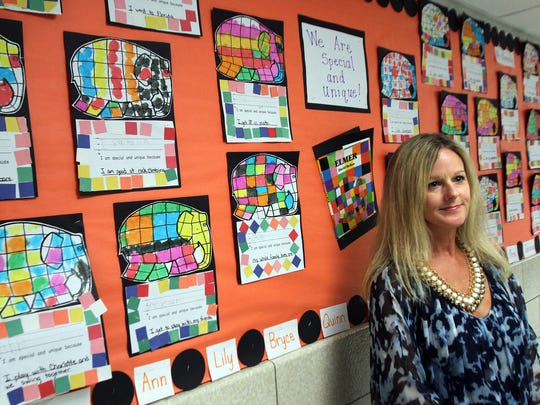 Adrianne Hoban is shown next to a bulletin board inside
