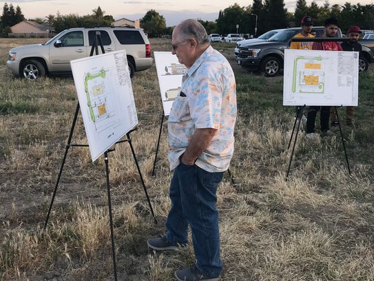 Tom Rings looks at drawings for a proposed Arco AMPM