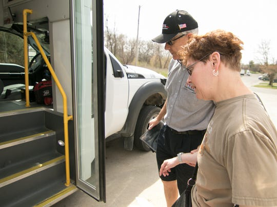 L.E.T.S. bus driver Winston Gee helps Linda Mason aboard