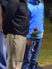 Christopher Hagedorn stands with his father Brad Hagedorn as he is recognized for his dedication to the golf team.