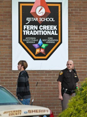 A Jefferson County Sheriff's deputy keeps watch in front of Fern Creek High School as students arrive for class after Tuesday's shooting where a 16-year-old Fern Creek High School student is accused of shooting a 15-year-old student. The 16-year-old faces numerous charges, including assault and wanton endangerment. The 15-year-old is still hospitalized with non-life threatening injuries. Oct.1, 2014