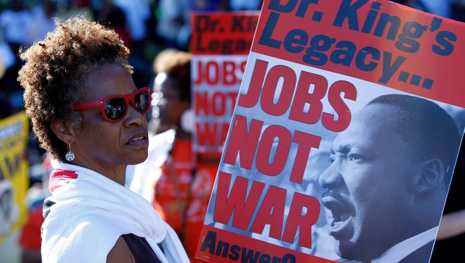 Claudia Hanes from Kentucky holds a placard during a rally to commemorate the 50th anniversary of the 1963 March on Washington at the Lincoln Memorial in Washington.