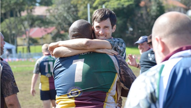 Luke Anderson, facing camera, gets a hug from Grizzlies Rugby Football Club teammate Will Harmon at the 2014 Bingham Cup held in Sydney, Australia. The biennial event is being held in Nashville in May.