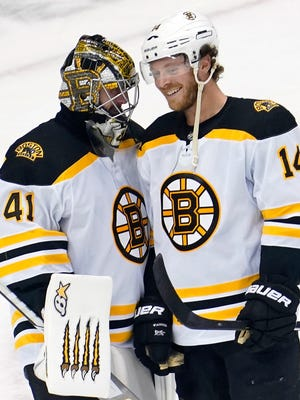 Boston Bruins right wing Chris Wagner (14) smiles while talking with goaltender Jaroslav Halak (41) after their win over the Carolina Hurricanes in game three of the first round of the 2020 Stanley Cup Playoffs at Scotiabank Arena on Aug. 15, 2020.