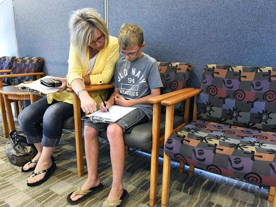 Pamela McIver, Foley, and her son Tanner, 11, fill out the questionnaires and paperwork before Tanner gets his vaccinations July 20 at CentraCare Health Plaza.
