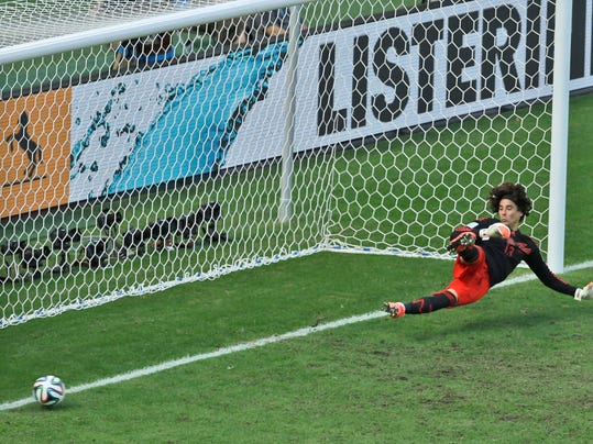 Mexico's goalkeeper Guillermo Ochoa fails to save a shot by Netherlands' Klaas-Jan Huntelaar from the penalty spot during the World Cup round of 16 soccer match between the Netherlands and Mexico at the Arena Castelao in Fortaleza, Brazil, Sunday, June 29, 2014. Holland won 2-1 and advanced to the quarterfinal.  (AP Photo/Themba Hadebe)