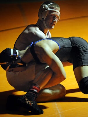 Trevor Wittmus of Valders, top, wrestles against Bryce Herlache of Wrightstown in their 160-pound finals match during the Olympian Conference wrestling tournament on Saturday, Feb. 7, 2015 at Mishicot High School in Mishicot.