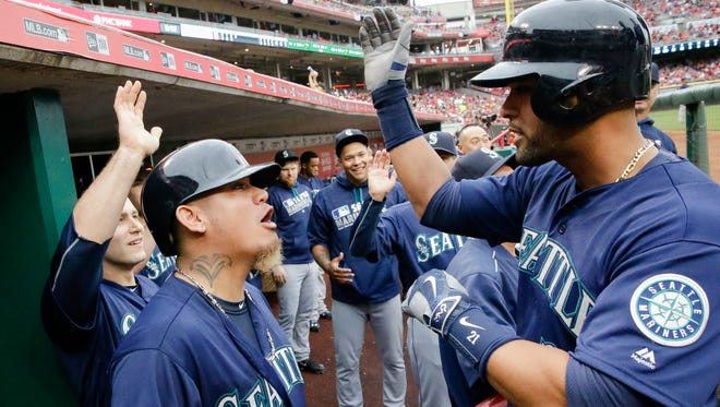 Seattle Mariners' Franklin Gutierrez, right, celebrates with Felix Hernandez, second from left, and teammates in the dugout after hitting a three-run home run off Cincinnati Reds starting pitcher John Lamb in the fourth inning of a baseball game, Saturday, May 21, 2016, in Cincinnati. (AP Photo/John Minchillo)