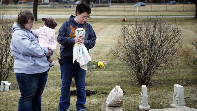 Rachel and Heidi McFarland stand with their newly adopted daughter Wednesday, March 25, 2015, at the unmarked grave of Gabriel King McFarland, a baby they tried to adopt that was killed last year.