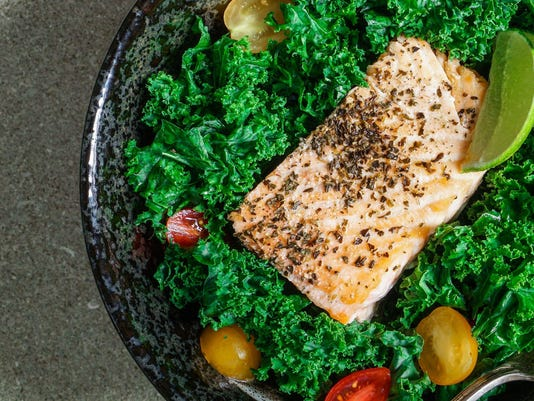 Healthy kale salad with baked salmon.