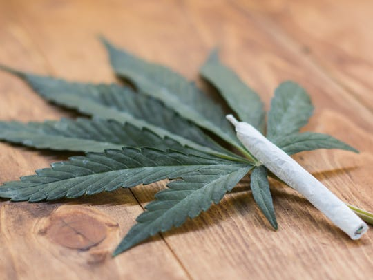A rolled cannabis joint propped up next to a cannabis leaf on a table.