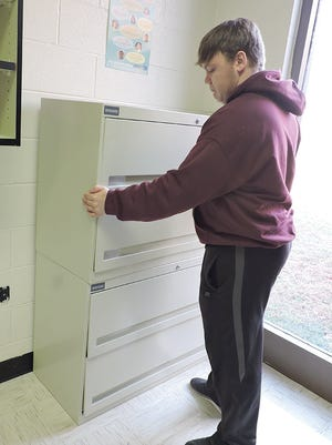 Fairview High senior Ben Jones installs cabinets in the Learning Lab, a room accessible to any student for computer usage, testing and credit recovery. The new cabinets house instructional materials and credit recovery folders.