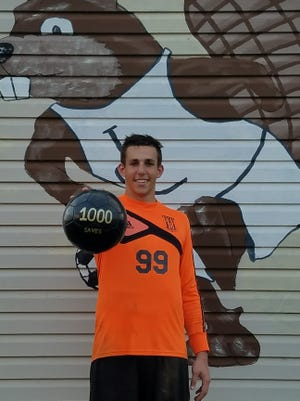 Lebanon Catholic boys soccer goalie Nate Hatzfeld poses with a soccer ball commemorating his 1,000th career save.
