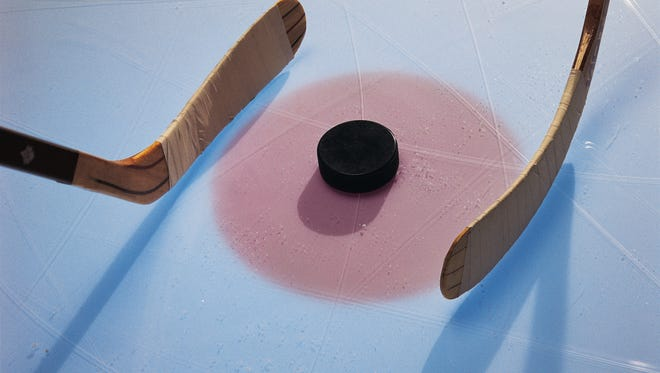 Ice hockey puck and sticks in face-off