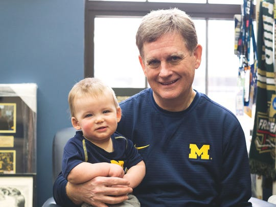 Michigan hockey coach Mel Pearson plays with his grandson, Finnely, at his office in Ann Arbor.