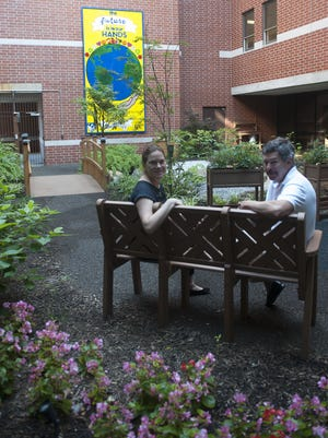 Garden designer Jack Carman and Amy Quick, director of the CASTLE Program, sit at the meditation garden designed by Carman and created by Virtua to comfort and support Alzheimer's patients.