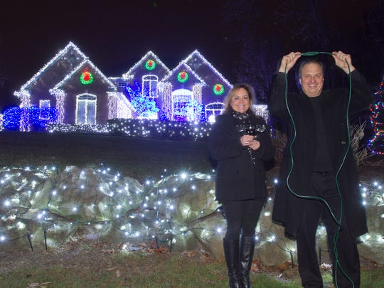 "Donna and Greg Sauchak re-enact a scene from National Lampoon's ""Christmas Vacation"" by pretending to plug in the lights that in the movie do not light up. Donna holds a glass of wine shaped like a moose, just like in that movie as well. The Sauchaks light up their home at 4109 Dominion Blvd. in Brighton with a ceremony reminiscent of the scene in that movie every year, an event that drew maybe 100 neighbors this year."