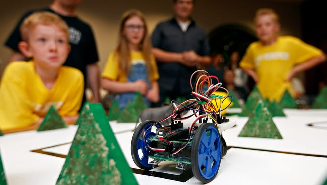 (from left) Thomas Daniel, 8, Gene Burdette, Jessalyn Gann, 11, Daniel Douglas and Gavin Crawford, 12, watch as their team's robot tries to navigate a test course during a robotics competition held by 417 Robotics at The Library Center in Springfield, Mo. on April 30, 2016. The yellow team finished tied for first.