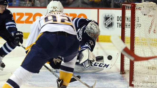Jets goalie Connor Hellebuyck (30) looks for a loose puck after Predators forward Kevin Fiala (not shown) scores in the first period Thursday.