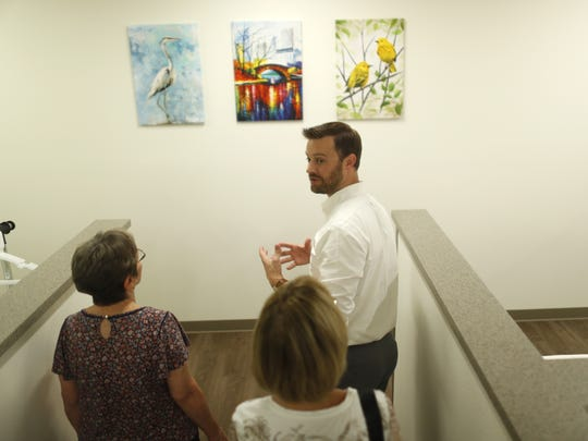 Circle the City CEO Brandon Clark (center) leads a tour with Sister Adele O'Sullivan (L) and Annette Stein at Circle the City's new facility in Phoenix, Ariz. on Aug. 9, 2018.