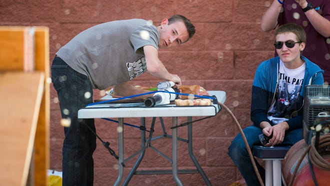 Cameron Ribail (left) fires a potato at a tennis racquet while Wyatt Carlowe watches at Fountain Hills High School on May 7, 2014. The students were attempting to break the Guinness Book of World Record of 17 for the number of potatoes fired with a potato gun through a tennis racquet under three minutes.