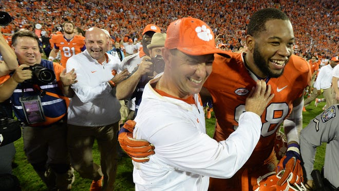 Clemson head coach Dabo Swinney hugs defensive tackle Kevin Dodd (98) after the Tigers 23-13 win over Florida State Saturday, November 7, 2015 at Clemson's Memorial Stadium.