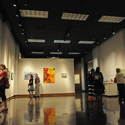 Folks look at art during the Excellence in Art opening reception held at the Louisiana State Exhibit Museum.