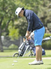 Redwood's Nike Phan putts on the 14th hole during the Visalia Boys Golf Tournament.