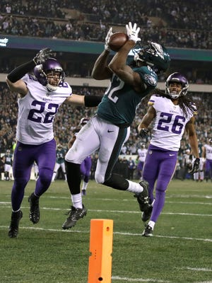 Philadelphia Eagles' Torrey Smith catches a touchdown pass in front of Minnesota Vikings' Trae Waynes (26) and Harrison Smith (22) during the second half of the NFL football NFC championship game Sunday, Jan. 21, 2018, in Philadelphia.