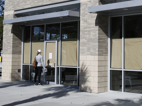 """A woman reads a message from the owners posted on the door at Vertigo Burger on Market Street Tuesday that explains that renovations were ongoing inside to convert the restaurant into a new """"breakfast and lunch concept."""""""