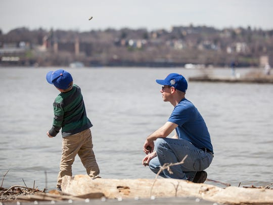 Peter Sine of Beacon and his son Joseph, 6, throw pebbles and rocks together as they enjoy the warm weather on the Hudson River at Long Dock Park in Beacon, April 10, 2017