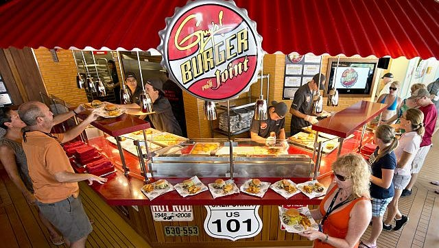 Guests aboard Carnival Breeze carry custom-made hamburgers and fries prepared at Guy's Burger Joint, a free burger venue developed in partnership with Food Network personality Guy Fieri.