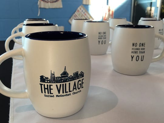 Visitors to The Village receive coffee mugs and magnets along with hearty greetings from T-shirt-wearing volunteers.