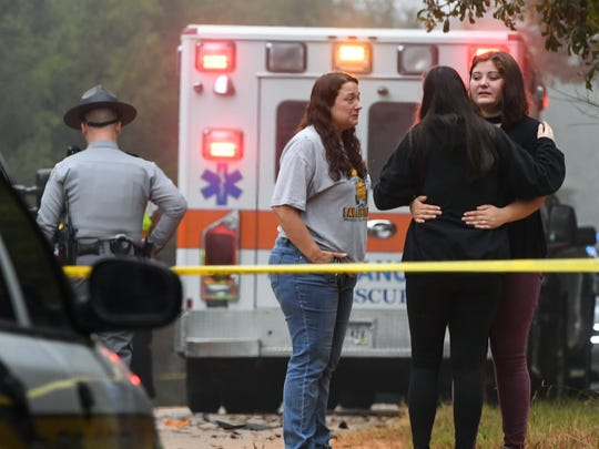 People hug at the scene auto accident, in which a pedestrian died at a school bus stop, on First Avenue in Starr on Monday morning.