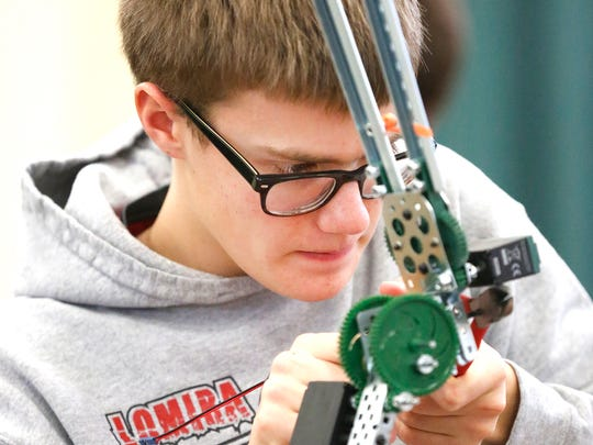 Ian Van der Grinten of Lomira makes an adjustment to his robot Saturday morning at the fourth-annual Ishamon Harris Memorial VEX Robotics Competition Tournament held at the Fond du Lac Fairgrounds.
