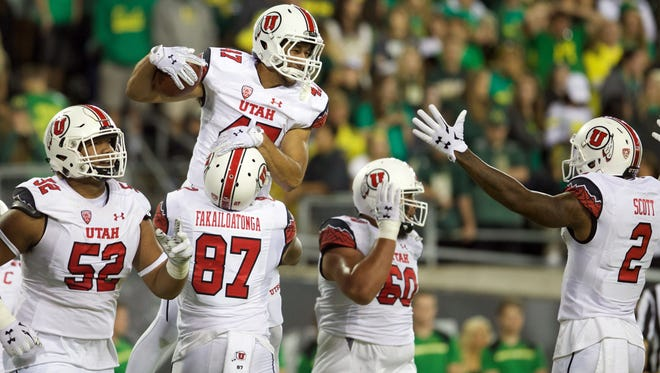 Utah tight end Caleb Repp celebrates a touchdown with teammates during their game against Oregon at Autzen Stadium in Eugene, Ore.