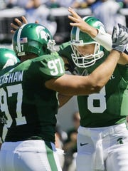 MSU quarterback Kirk Cousins (right) celebrates with