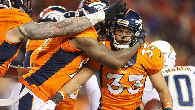 Denver Broncos defensive back Shiloh Keo (33) celebrates with teammates after intercepting a pass during the second half against the San Diego Chargers at Sports Authority Field at Mile High.
