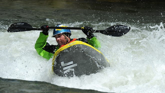 Kayaker Stephen Wright plays on a wave at the Truckee River Whitewater Park in downtown Reno on April 25, 2016.