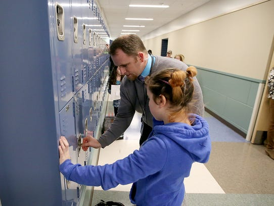 Assistant Principal Todd Hering helps a student open