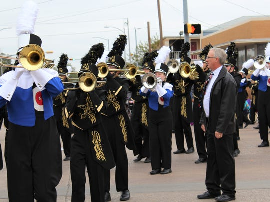 Retiring Abilene High School band director Paul Walker watches a combined unit of AHS and Cooper band members march in a downtown parade.