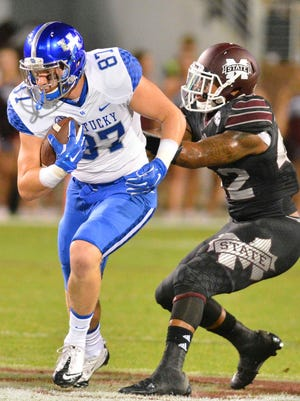 Oct 24, 2015; Starkville, MS, USA; Kentucky Wildcats tight end C.J. Conrad (87) runs the ball as he is defended by Mississippi State Bulldogs linebacker Beniquez Brown (42) during the first quarter of the game at Davis Wade Stadium.