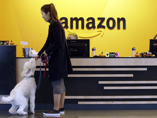 An Amazon employee gives her dog a biscuit as the pair head into a company building, where dogs are welcome, in Seattle.