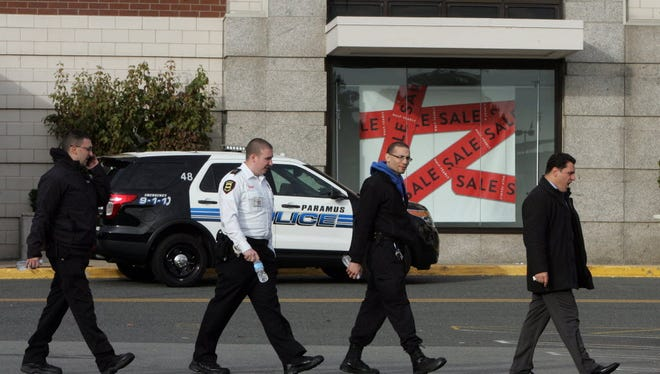 A group of men who looked like mall security exit the mall near Nordstrom's store this morning. The mall was closed this morning as police were still investigating the scene, and there were many cars still parked in the mall's lot. 20-year-old Richard Shoop of Teaneck walked into the Westfield Garden State Plaza mall in Paramus on Monday night and fired six shots, setting off a panicked frenzy and a six-hour manhunt, was found in a storage area inside the shopping center early Tuesday morning with a self-inflicted gunshot wound to his head.
