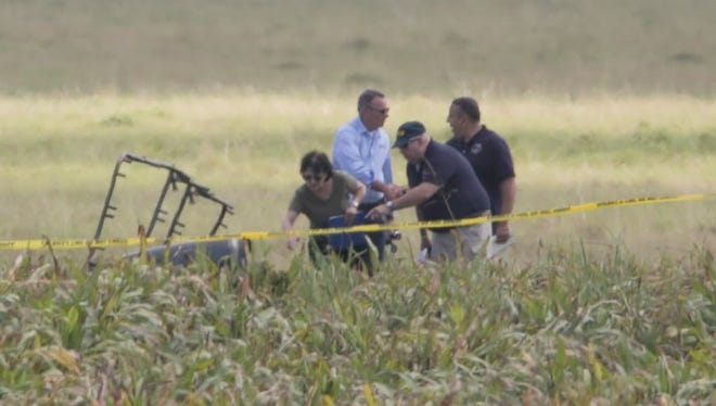 The partial frame of a hot air balloon is visible above a crop field as investigators comb the wreckage of a crash Saturday morning, July 30, 2016, near Lockhart, Texas.