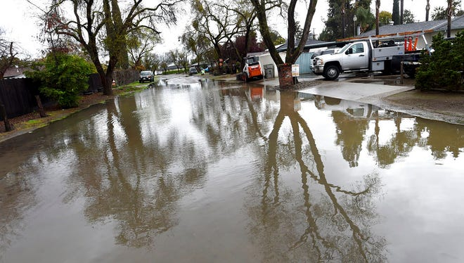 Tarpey Village streets are flooded Thursday, March 22, 2018, in Fresno, Calif. A powerful storm spread more rain across California on Thursday, flooding streets and threatening to unleash mud and debris flows into communities near areas burned bare by wildfires.