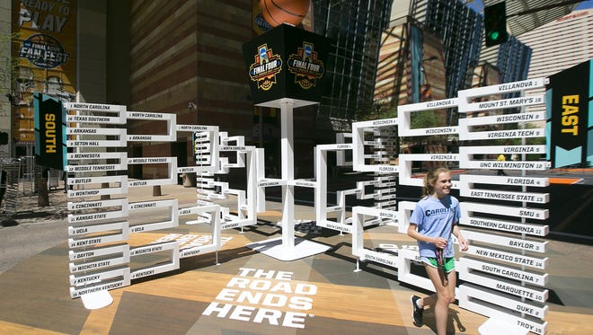 North Carolina fan Amanda Brickner, 12, of Chapel Hill, N.C., walks by the giant March Madness bracket outside the Phoenix Convention Center in downtown Phoenix on March 29, 2017.