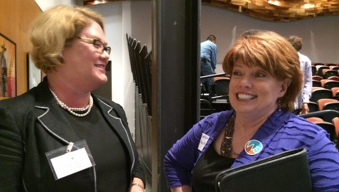 In this 2015 file photo, Kristi Hall, left, owner of Conscious Connections, a Phoenix consulting firm, talks with job hunter Cic Cicolello, 50, of Tempe, at the BestCompaniesAZ Womens Career Event in Scottsdale.
